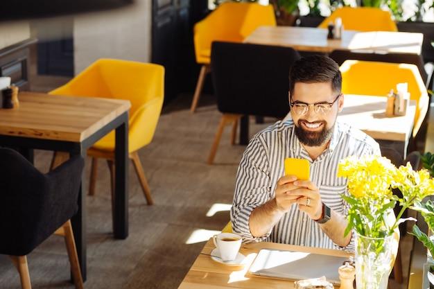 온라인 채팅. 그것에 메시지를 입력하는 동안 그의 스마트 폰 들고 행복 수염 된 남자