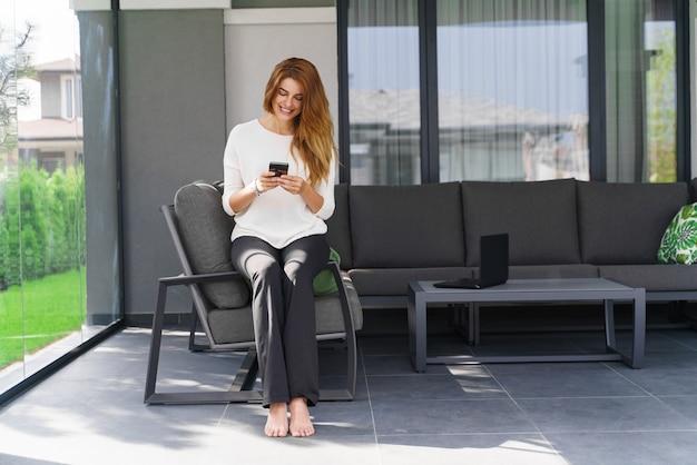 온라인 채팅. 테라스에서 현대적인 스마트폰을 사용하여 웃고 있는 젊은 여성. 안락의 자에 앉아 있는 동안 메시지를 확인 하는 예쁜 갈색 머리 소녀. 가정 생활 개념