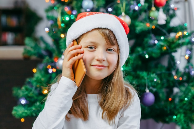 Online christmas greetings. a close-up portrait of a cute girl in a new year's hat with a mobile phone. the child uses gadgets to congratulate family and friends.