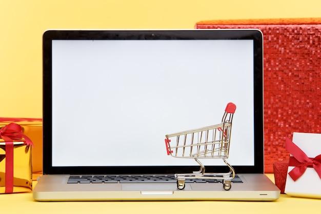 ノートパソコンのディスプレイ上のオンラインクリスマスショッピングのコンセプト。白い画面。