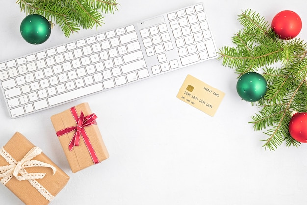 ギフトボックス、キーボード、ゴールデンクレジットカードを使ったオンラインクリスマスショッピングのコンセプト。上面図、フラットレイ