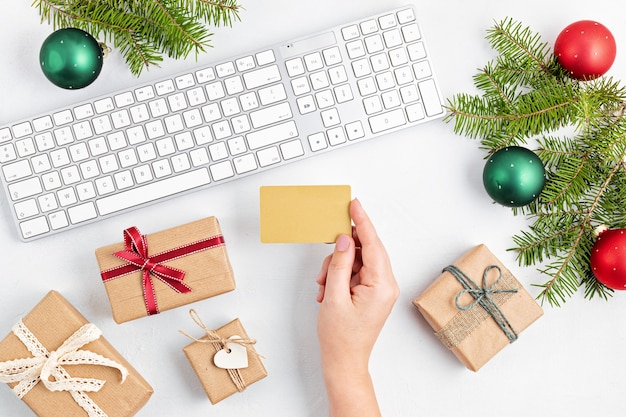 Online christmas shopping with gift boxes, keyboard and mockup of golden credit card