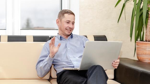 オンラインコミュニケーション。ソファに座っている青いシャツを着た若いマネージャーが、ラップトップを膝に抱えてコミュニケーションを取ります。