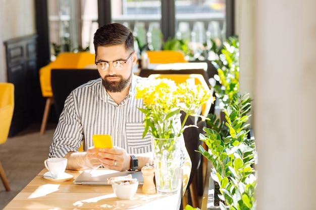온라인 커뮤니케이션. 카페에 앉아있는 동안 그의 현대적인 스마트 폰을 사용하는 좋은 잘 생긴 남자