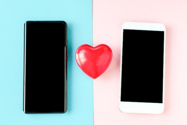 オンラインコミュニケーション、仮想愛、孤独なウェブインターネット、愛のテキストメッセージ、メッセージング、オンラインデート。聖バレンタインデーのコンセプト。バレンタインデーコロナウイルス2台の電話とハート。 covid19バレンタイン。