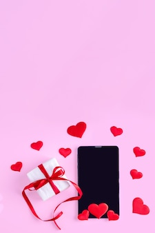 Online congratulations concept. black blank tablet or phone screen with red heart shape and gift