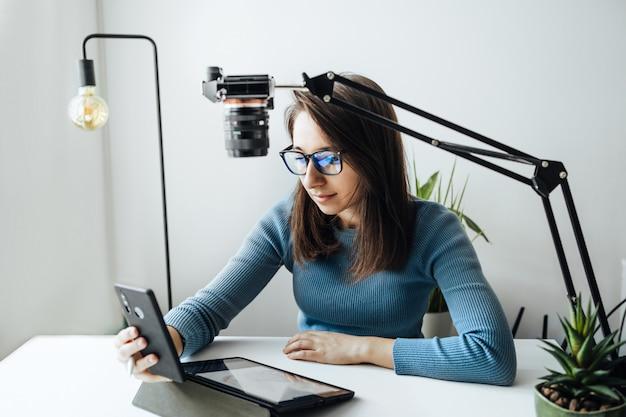 オンラインコンテンツクリエーターのvlogger。眼鏡をかけた若い女性のブロガーが、ブログやトレーニングコースのコンテンツを削除しています。 walercolorを利用したオンライン学習のコンセプト