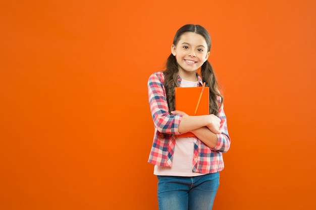 Online courses for kids. girl child hug textbook orange background. studying is fun. extra school course. school concept. pupil carrying textbook. language courses for youth. educational courses.