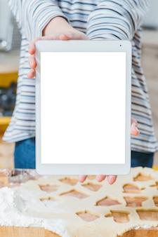 온라인 요리 코스. 흰색 태블릿 화면의 근접 촬영입니다. 테이블에 압 연된 반죽 위에 장치를 들고 여자.
