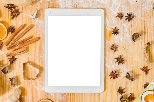 온라인 요리 코스. 흰색 화면이있는 태블릿의 평면 배치. 나무 테이블은 밀가루와 향신료로 덮여 있습니다.