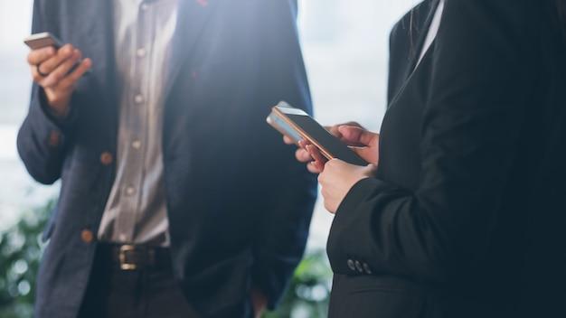 Распорядок дня в сети. обрезанный снимок коллег мужского и женского пола отвлекается со смартфонами.