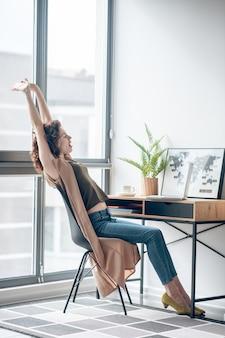 オンライン。手に電話で座っている黒髪の女性