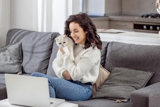 В сети. темноволосая молодая женщина обнимает своего кота и разговаривает по видеосвязи