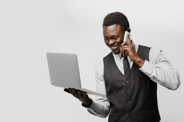 온라인 데이트 에이전시. 노트북과 전화를 가진 흑인 남성은 전 세계의 여성들과 이야기합니다. 인터넷에서 그의 사랑을 찾는 사업가.
