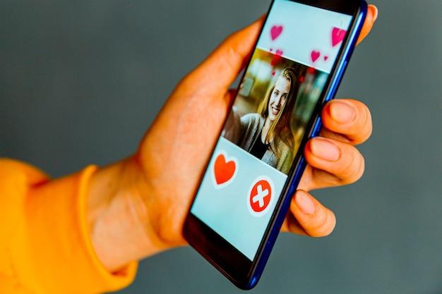 Приложение для онлайн-знакомств в смартфоне. мужчина смотрит на фото красивой женщины.