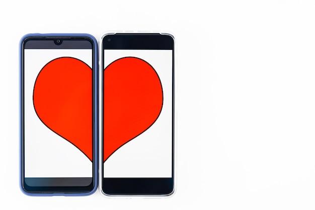 온라인 데이트 개념. 두 스마트 폰 화면에서 심장의 절반. 발렌타인 데이 컨셉