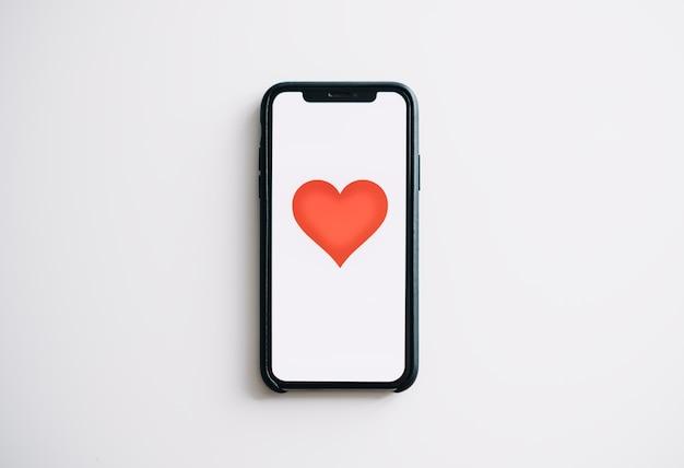 オンラインデートの概念。画面に赤いハートのスマートフォン。