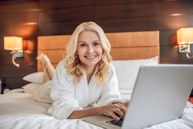 Online dating. pretty woman in a bath robe laying on bed with a laptop and typinga message