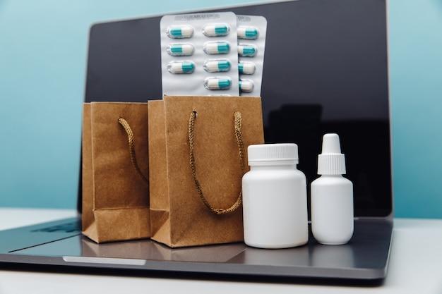 Онлайн-доставка и покупка концептуальных бумажных пакетов с лекарствами, отпускаемыми по рецепту, таблетками и контейнерами на ноутбуке на синем фоне