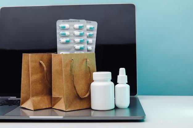 Интернет-доставка и концепция покупок. бумажные пакеты с лекарствами и таблетками, отпускаемыми по рецепту, и белыми контейнерами на ноутбуке на синем фоне.