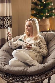 온라인 배송 등록. 선물 상자를 들고 온라인으로 크리스마스 선물을 배달하는 여자