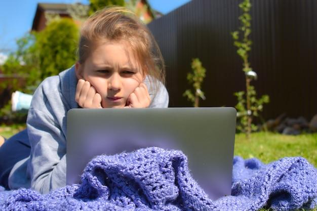 온라인 원격 학습 야외. 홈 스쿨링. 소녀는 숙제를 이해하지 못합니다.