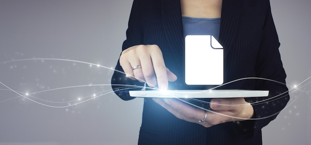 Online documentation database. white tablet in businesswoman hand with digital hologram document sign on grey background. corporate data management system.