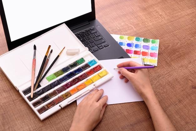 紙のペンキと木製のオフィスのブラシのラップトップシートでオンライン描画クラスカバーの概念...