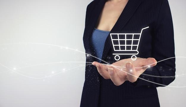 Online e-commerce shopping concept. hand hold digital hologram shopping cart