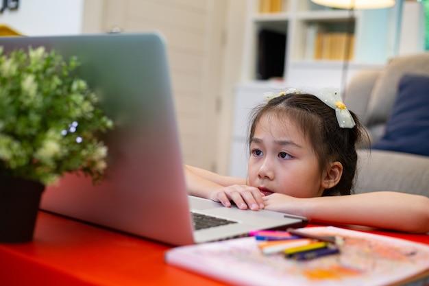 온라인 교육입니다. 거실에서 배우고 공부하기 위해 노트북을 사용하는 아시아 아이입니다. 홈스쿨 개념입니다.