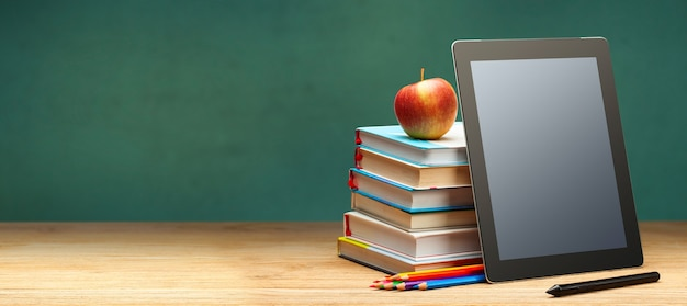 Online education. books and tablet on the desktop on blackboard background. copy space for text.