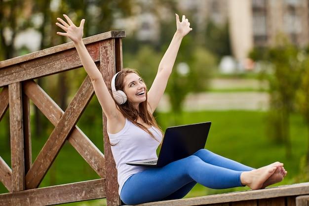 Онлайн-обучение веселой женщины в беспроводных наушниках с ноутбуком на открытом воздухе