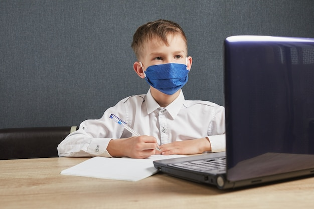 Концепция онлайн-образования. мальчик в маске изучает домашнее задание по математике во время онлайн-урока дома.