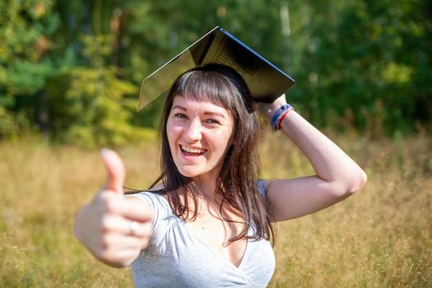 Студентка концепции онлайн-образования держит ноутбук над головой, как квадратную академическую кепку и
