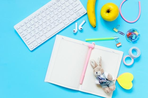 オンライン教育の概念青い背景にタブレット電話ヘッドフォンノートブック学用品