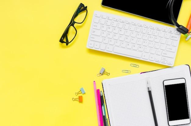 オンライン教育の概念。タブレット、電話、ヘッドフォン、ノートブック、黄色の背景に学用品。検疫中の遠隔学校。コピースペースを使用して上から表示します。モックアップ、フラットレイ