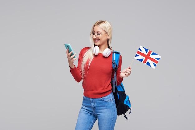 Образование онлайн, переводчик иностранного языка, английский, студент - улыбающаяся белокурая женщина в наушниках, держащая мобильный телефон и британский флаг. серое пространство, дистанционное обучение