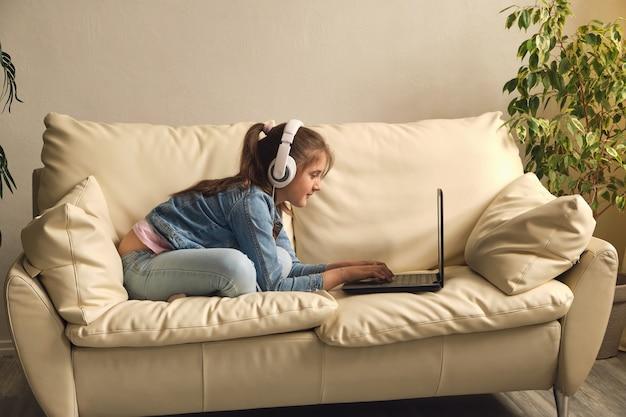 Онлайн-образование. малыш девочка с наушниками смотрит ноутбук конференции учителя видео урока, сидя на диване у себя дома