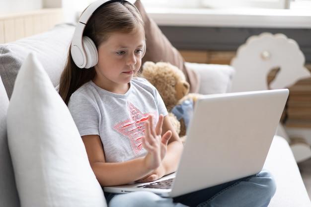 子供のオンライン教育。自宅のソファに座っているビデオレッスン教師会議ラップトップを探しているヘッドフォンを持つ甘い女の子。