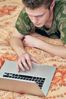 オンライン教育。男は隔離された家のソファに横になり、ラップトップを見る