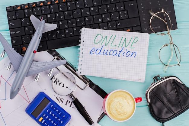 여행용 액세서리 안경 지갑과 비행기가 있는 노트북의 온라인 교육 단어는 나무 테이블 상단 배경에 있습니다. 상단 구성의 검은색 키보드입니다.