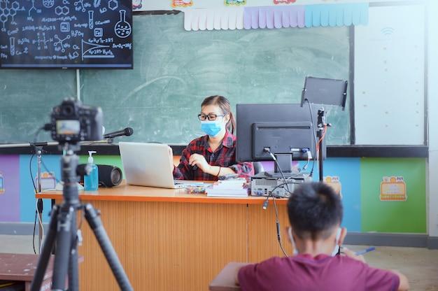 온라인 교육. 안면 마스크를 쓴 화상 통화 교사와 함께 온라인으로 project.study 작업, 사회적 거리두기, 새로운 정상적인 행동.