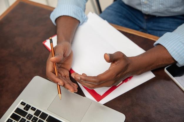 自宅でのオンライン英語コース。インテリアでリモートで学生を教える間、男の手を閉じます