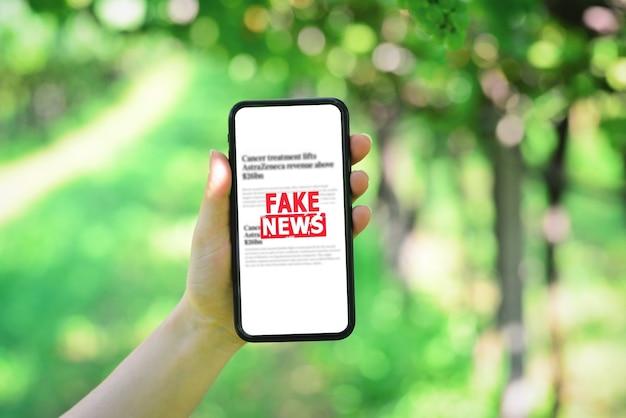 携帯電話でのオンラインフェイクニュースブドウ園の背景にフェイクニュースが付いたスマートフォンを持っている