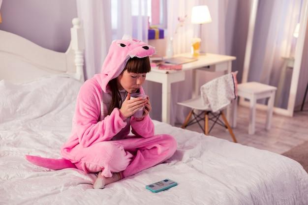Интернет-фильм. довольная брюнетка девушка в теплой пижаме, сидя на кровати