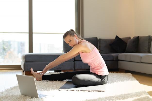 オンラインフィットネス。ノートパソコンの反対側のヨガマットで演習を行う若い女性