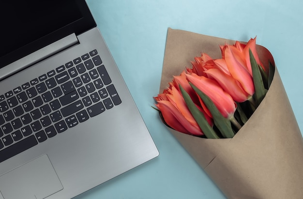 Online flower shop. bouquet of tulips with a laptop on blue