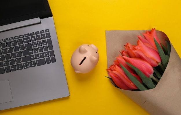 Online flower shop. bouquet of tulips with laptop, piggy bank on yellow