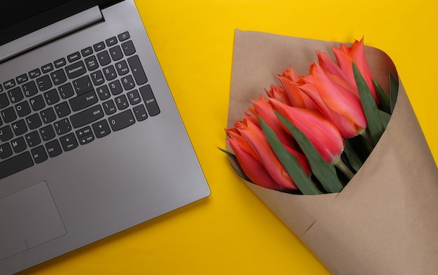 Online flower shop. bouquet of tulips with a laptop on a yellow