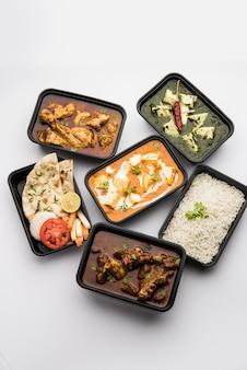 Концепция доставки еды через интернет индийский панир, масло масала и палак, карри с бараниной и курицей, роти и рис в пластиковых контейнерах, еда, такая как курица в масле, курица
